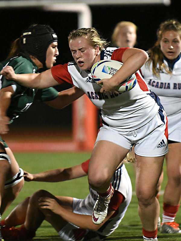 Acadia Rugby varsity athlete Sara Baxter drives forward at Raymond Field.