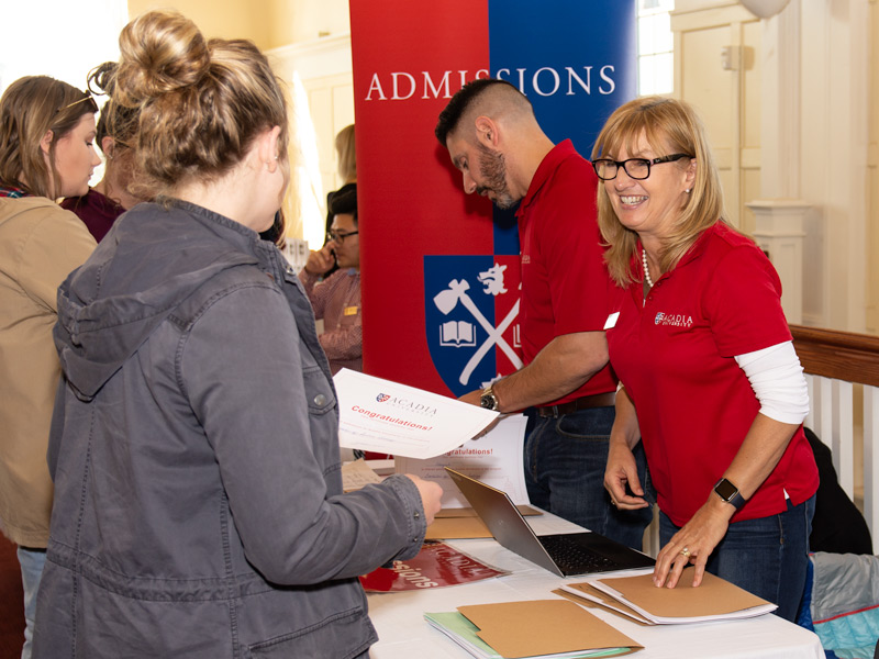 Prospective students speak with Acadia staff members at an Open House