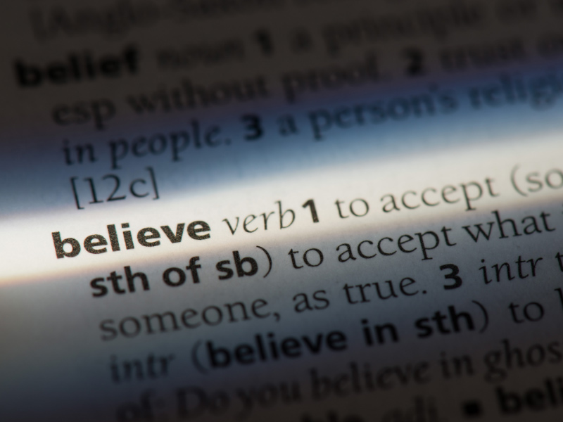 "A closeup of the word ""believe"" on the page of a dictionary."