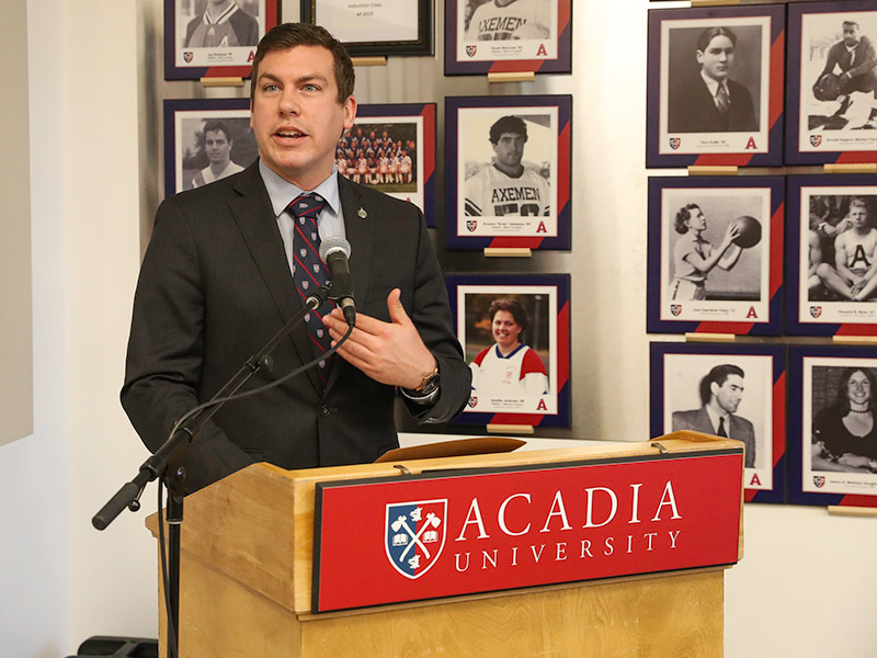 Kody Blois, Member of Parliament for Kings—Hants, speaks from a podium in the Alumni Room in the Acadia Athletics Complex