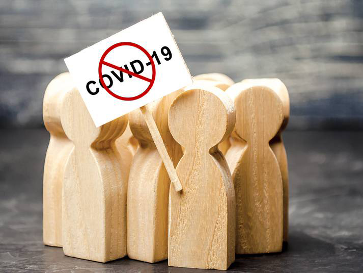 Wooden figures holding a 'No COVID-19' placard. RF Stock image licensed by Saltwire.