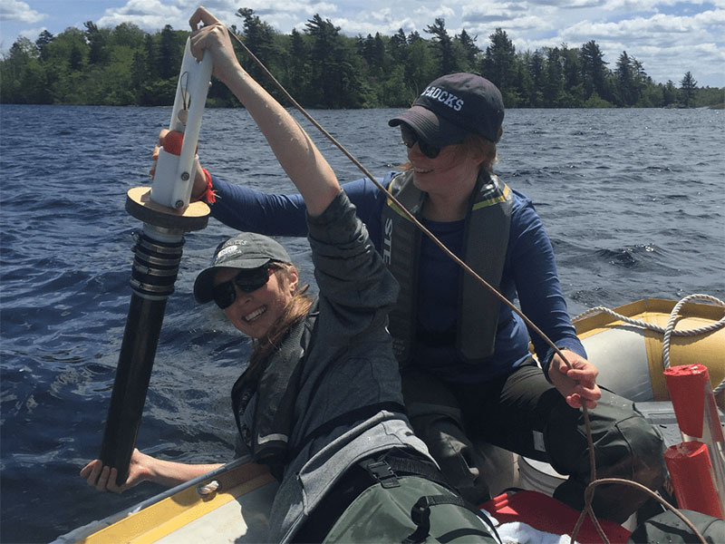 Julia Crews (left), BSc Honors ENVS '20, collecting a lake sediment core with a gravity corer on Gaspereau Lake, assisted by Lauren Muzak Ruff (right), MSc ENVS '21. Photo taken before COVID-19.