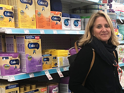 Professor Lesley Frank stands next to a shelf of infant formula in a supermarket. Photo courtesy of Mary-Catherine McIntosh/CBC.