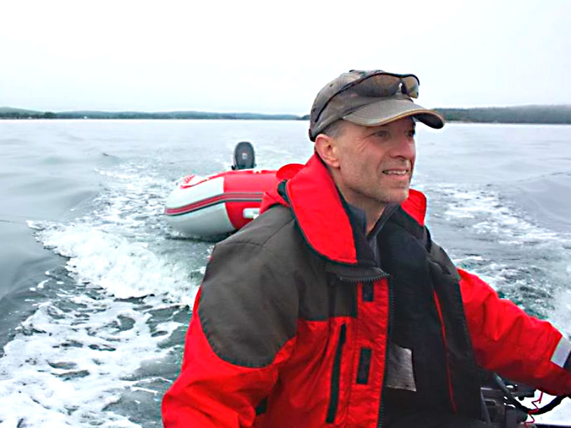 Dr. Mark Mallory smiles while piloting a boat