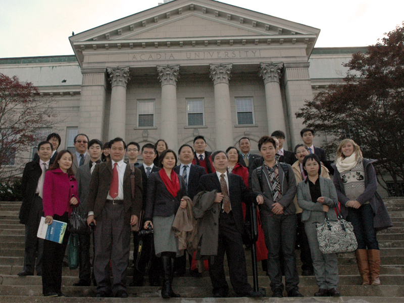 A group of international visitors gather on the steps of University Hall.