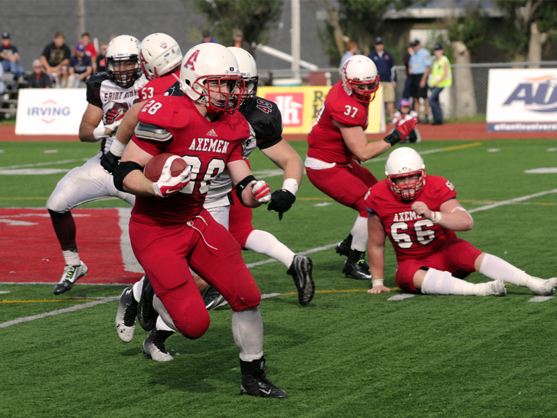 Acadia Axemen football players charge down the field.