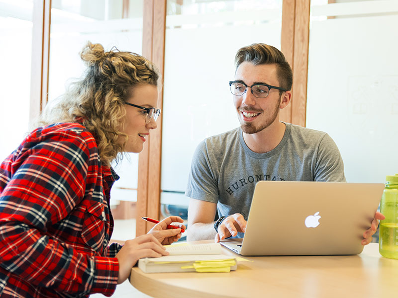 Two students work together with a book and a laptop in Patterson Hall