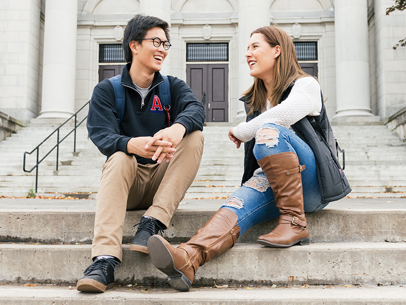 Two students chat on the front steps of University Hall