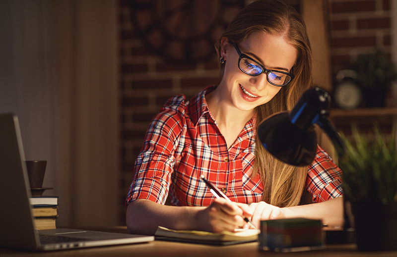 A female student smiles as she studies at home in the evening