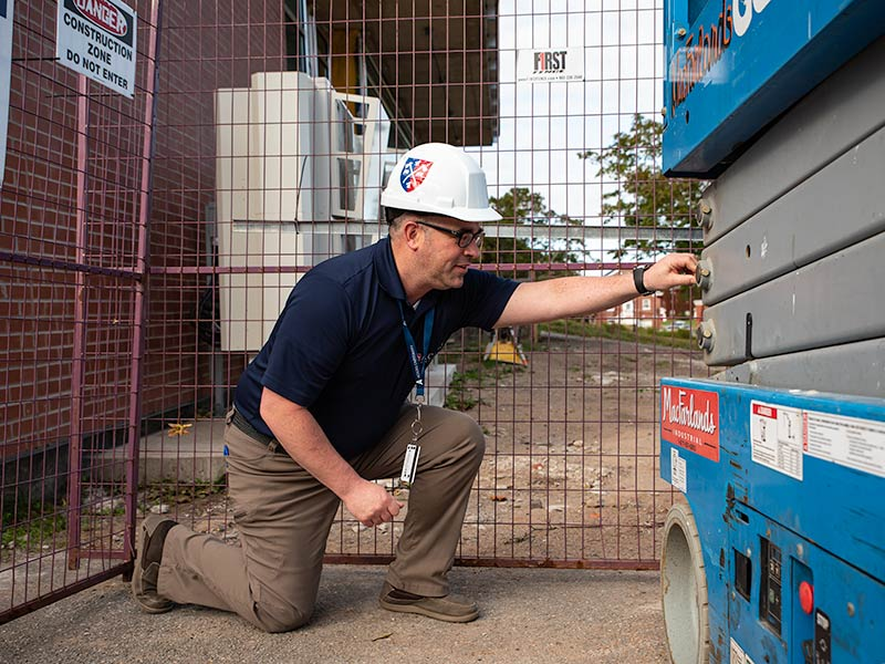 OHS Coordinator Greg Deveau inspects a campus construction site while wearing a hardhat.