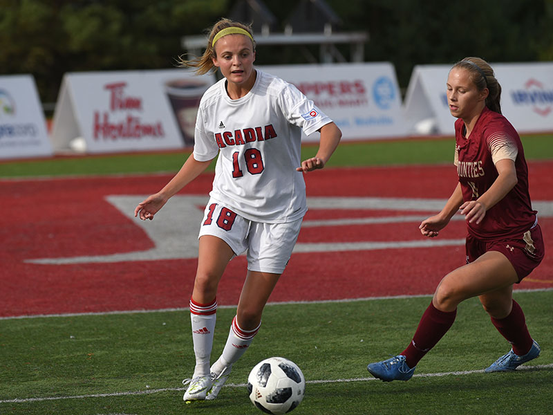 Acadia Axewomen Soccer's Allie Scovil presses forward with the ball.