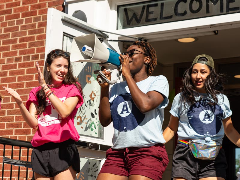Female RA's and Welcome Week leaders cheer for students to enter War Memorial House during Move-In Day 2019.